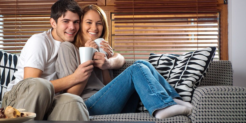 couple sitting on couch excited about new home incentives for their mortgage